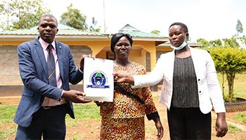 Kilimo loan beneficiary receives a gift from Imarisha Sacco Nandi Hills staff during a courtesy visit to her home in Nandi.